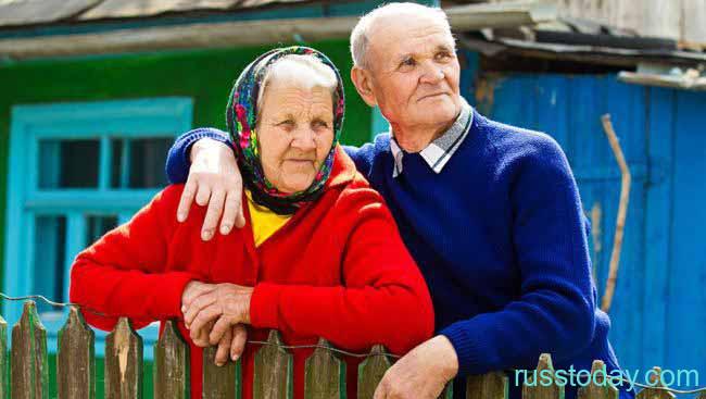 Пенсионеры на фоне частного дома